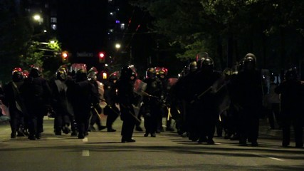 Group of riot officers marching military step and hit batons