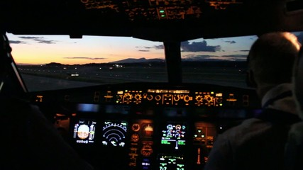 Pink sunset viewed from airplane cockpit with dashboard lights