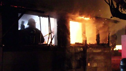 Fire fighters battling house fire at night with flames showing