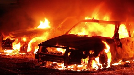 Two police cars fully involved in flames at night in parking lot