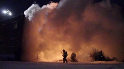 Firemen in silhouette walking out of large orange cloud of smoke