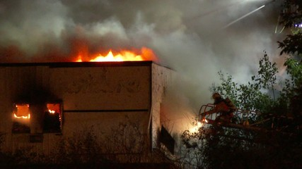 Fireman using pike pole to open wall and ventilate building fire