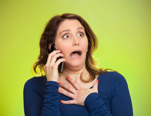 Woman receiving shocking news on a phone, green background