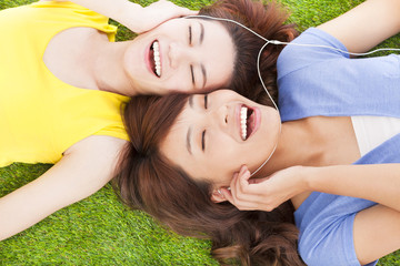 two pretty young woman lying on grassland and listening music