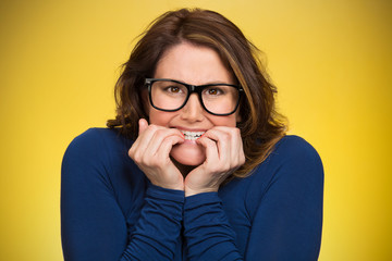 Anxious insecure woman, isolated on yellow background