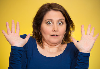 Shocked scared middle aged woman, yellow background