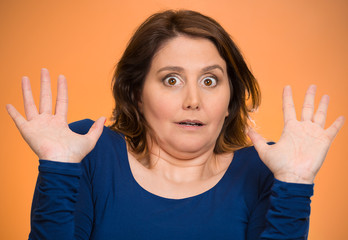 Shocked scared middle aged woman, orange background