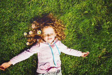 Curly girl lies on the grass and smiling, toning photo.