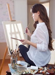 female artist with oil colors and brushes