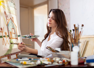 woman paints  on canvas in workshop
