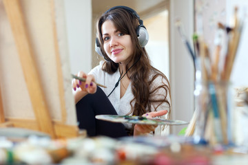 girl in headphones  paints with oil colors