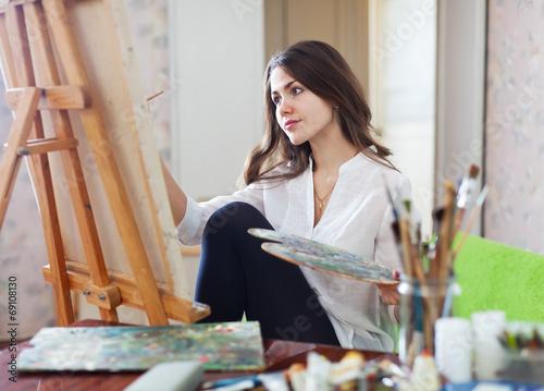 Leinwandbild Motiv Long-haired female artist paints with oil paints