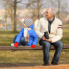 Grandfather shows grandson retro camera