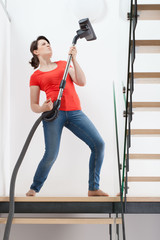 Girl having fun during vacuuming floor