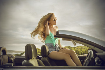 beautiful blonde woman sitting on a car