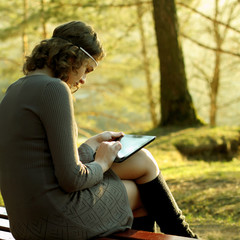 Hipster girl using tablet sitting near a tree at sunset