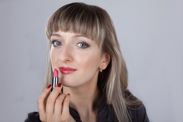 beautiful woman paints her lips