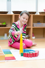 Little girl hand building tower made of montessori educational m