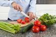 Woman cutting tomato