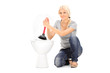 Young woman holding a plunger seated by a toilet