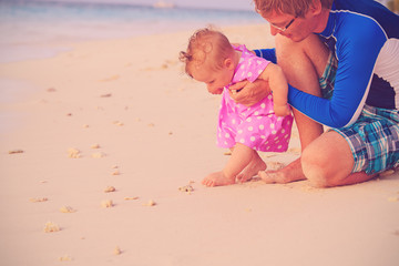 father and baby touching seashell on beach