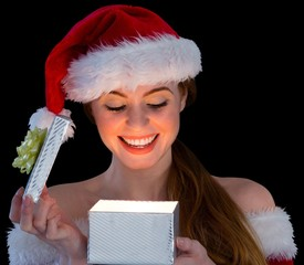 Pretty redhead in santa outfit opening a gift