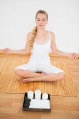 Peaceful blonde sitting in lotus pose on bamboo mat