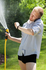 Man watered garden and talking on the phone