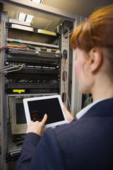 Pretty technician using tablet pc while fixing server