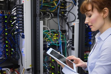 Technician using tablet pc while analysing server