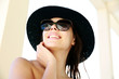 Portrait of a cheerful woman in sunglasses and hat