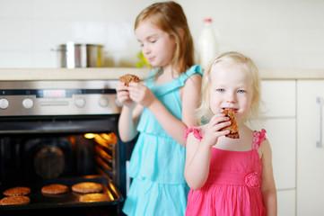 Two little sisters eating freshly baked cookies