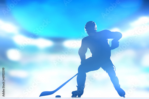 Hockey player skating with a puck in arena lighs