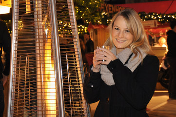 Frau trinkt Punsch auf Weihnachtsmarkt