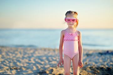 Adorable little girl having fun on a beach