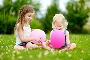 Two little sisters having fun wiith balloons
