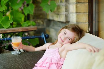 Adorable little girl drinking orange juice