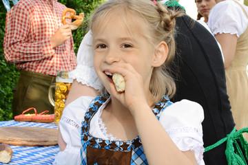 Mädchen im Dirndl isst Laugen-Brezel