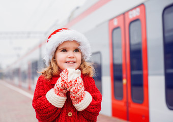 Little girl in red Santa costume on the train platform