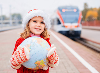 Happy little Santa with a globe waiting for a train