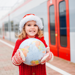 Happy little Santa travelling with a globe