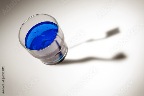 canvas print picture Blaues Wasser im Glas mit Zahnbürsten Schatten