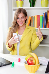 Beautiful young woman putting thumbs-up in the office