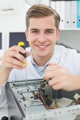 Computer engineer working on broken device with screwdriver