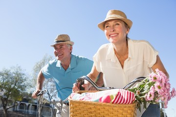 Happy senior couple going for a bike ride in the city