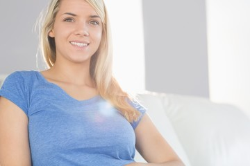 Smiling young woman sitting on sofa in the living room