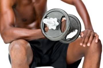Mid section of fit shirtless man lifting dumbbell