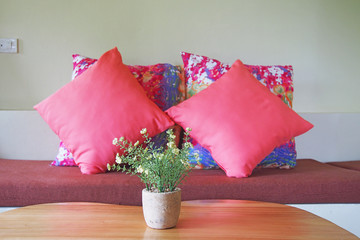 artificial flower in front of pink pillows on sofa