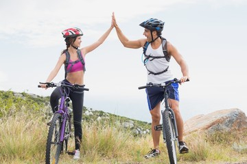 Athletic couple mountain biking while high fiving