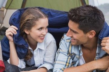 Happy young couple lying in tent